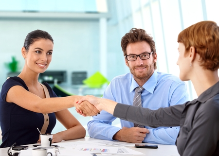 Young, attractive caucasian business people shaking hands on a successful deal at office meeting. Sitting at table, smiling. photo