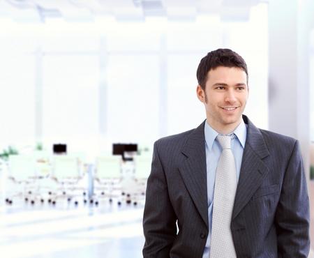 Glückliche junge kaukasisch Geschäftsmann in Anzug und Krawatte am hellen Büro. Stehen, Lächeln, Exemplar.