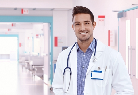 Happy young physician doctor standing at hospital hallway.\ Smiling, looking at camera, wearing stethoscope and lab coat.\ Copyspace.