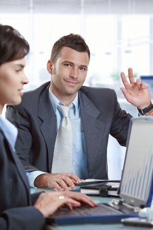 Caucasian businessman raising hand up at office business meeting. Sitting at table, looking at camera, suit and tie, focus in background. photo