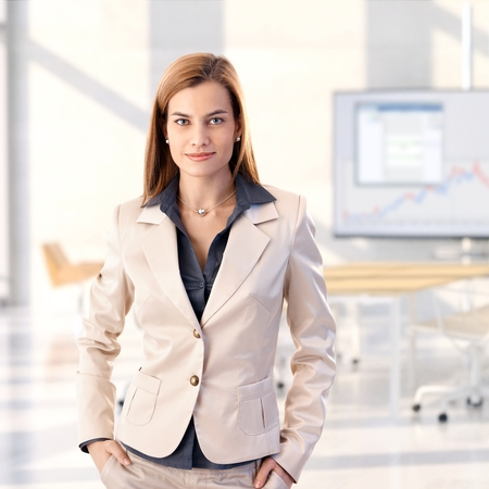 Confident caucasian blonde young businesswoman standing at bright office, smiling, looking at camera, hands in pocket, woman suit, copyspace. photo