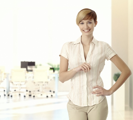 Portrait of happy caucasian casual blonde young business office manager. Standing, smiling, looking at camera, hand on hip, copyspace.