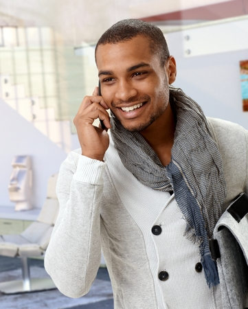 Trendy casual afro american man talking on mobile phone at home. Smiling, standing. Stock Photo