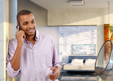 Casual handsome afro american man with mobile phone at trendy home. Standing against wall, smiling, happy, talking.