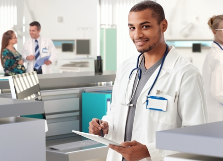 Happy, smiling handsome afro american doctor at hospital ward. Standing. looking at camera, wearing lab coat, stethoscope, name tag, tablet in hand. photo