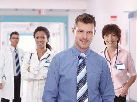 Portret van jonge vertrouwen ziekenhuis manager met medisch team. Glimlachen, staand, kijkend naar de camera, het dragen van stropdas.