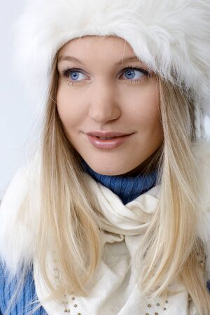Winter portrait of attractive young blonde woman smiling, looking away. photo