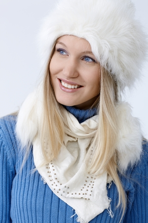 Winter portrait of happy young blonde woman in fur hat, looking away. photo