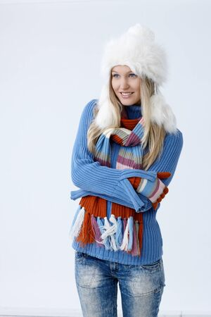 folding arms: Happy young woman in hat gloves and pullover freezing, folding arms around herself, looking away.