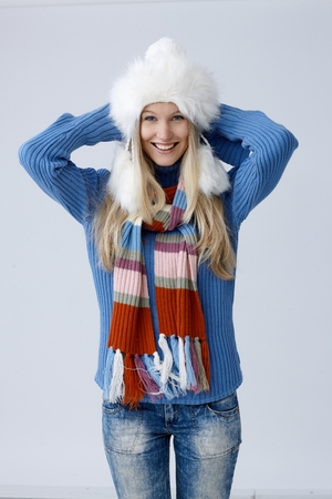 folding camera: Happy young blonde woman standing in hat and scarf, folding arms around scruff, smiling, looking at camera.