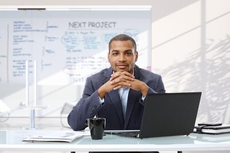 アフロ笑みを浮かべて自信実業家でラップトップ コンピューターのスタートアップのビジネス オフィスの机に座ってカメラ目線します。