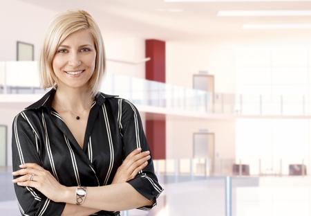 Elegante toevallige blonde Medio volwassen zakenvrouw op busines office center, armen gekruist, lachend, kijkend naar de camera, copyspace.