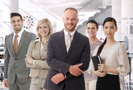 Group of successful business people at bright office, standing, smiling, happy, looking at camera. Suit. photo