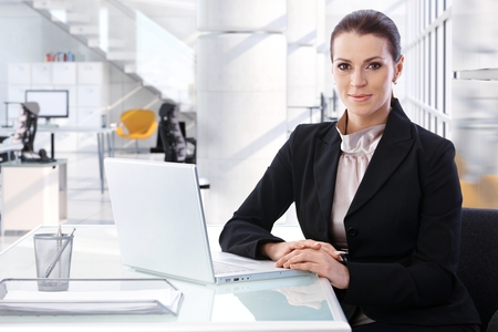 Aantrekkelijke medio volwassen brunette zakenvrouw zittend aan tafel met laptop computer op heldere high-tech business center office. Lachend, kijkend naar de camera, vrouw pak. Stockfoto