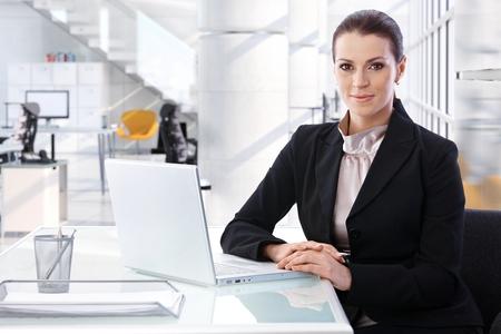 Aantrekkelijke medio volwassen brunette zakenvrouw zittend aan tafel met laptop computer op heldere high-tech business center office. Lachend, kijkend naar de camera, vrouw pak. Stockfoto