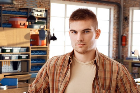 bristly: Portrait of confident casual young bristly caucasian student at DIY workshop. Looking at camera. Stock Photo