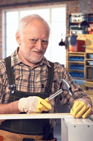 Happy caucasian pensioner hammering at DIY home workshop. Looking at camera, smiling. photo
