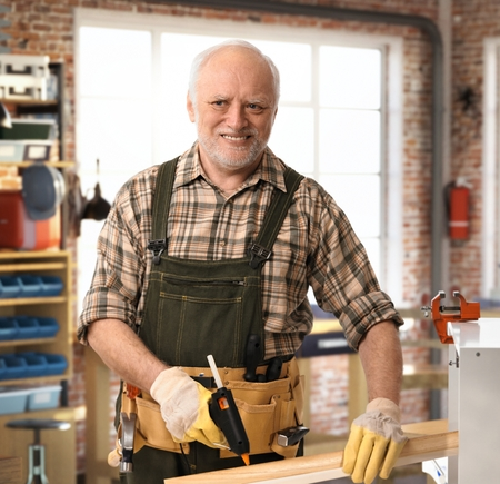 Senior happy casual caucasian handyman working at DIY workshop with tools, belt, wearing gloves. Smiling.