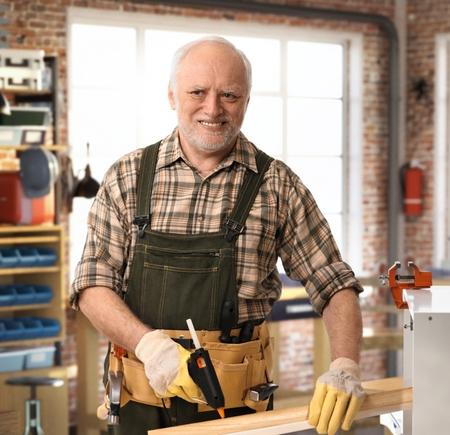 Senior caucasiano handyman feliz trabalhando na oficina DIY com ferramentas, cinto, luvas. Sorrindo.