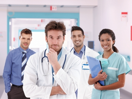 image consultant: Group portrait of happy doctors at hospital hallway. Handsome man, standing, smiling, looking at camera, wearing lab coat and stethoscope.