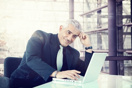 mid adult men: Smiling businessman sitting at office desk working with laptop. Stock Photo