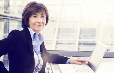 Portrait of senior businesswoman with laptop at office, Large copyspace.