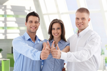 thumbup: Successful young caucasian casual startup business team giving thumbs up at financial center. Smiling, standing, looking at camera.