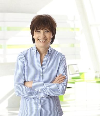 Mulher de negócios sênior caucasiano de pé com os braços cruzados no escritório brilhante. Sorrindo, olhando a câmera, copyspace.