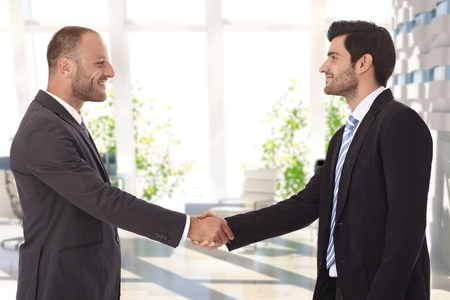 bristly: Bristly caucasian businessmen shaking hands on successful deal at bank center lobby. Smiling, standing, wearing suit and tie. Stock Photo