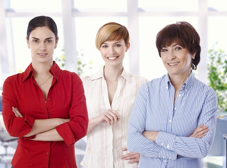 Group portrait of confident casual female caucasian business office workers. Smiling, arms crossed, looking at camera. photo