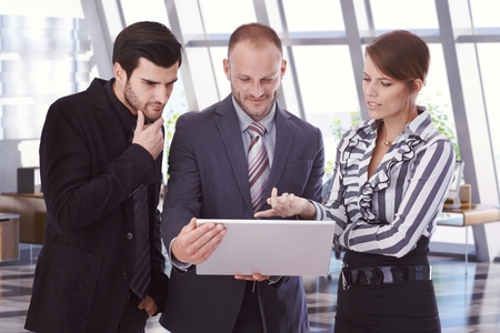 bristly: Caucasian business people looking at laptop computer screen at office. Bristly businessmen in suit and businesswoman pointing at screen. Standing. Stock Photo