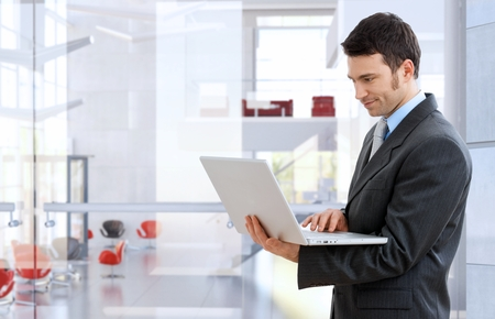 smirking: Confident caucasian stock broker standing and working with laptop at bright business office. Smirking, standing, suit and tie,