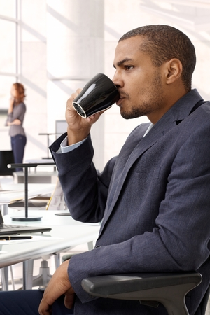 Serious afro american businessman drinking coffee at office. Sitting in chair, unsmiling. Side view, suit. photo