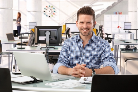Happy casual successful caucasian business consultant at startup office, sitting at table with laptop computer, smiling, confident, looking at camera, Imagens