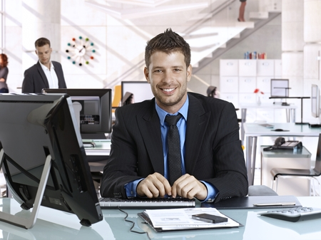Happy young rookie caucasian businessman at business office with computer, sitting behind desk, smiling, looking at camera, suit and tie. photo