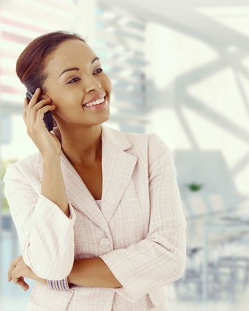 Attractive, elegant afro american businesswoman with mobile phone. Smiling, standing, warm colors. Copyspace. photo