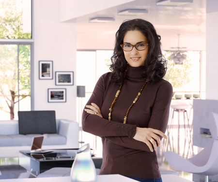 Happy attractive female casual caucasian interior designer at trendy luxury home, wearing glasses, standing arms crossed, looking at camera, smiling. photo