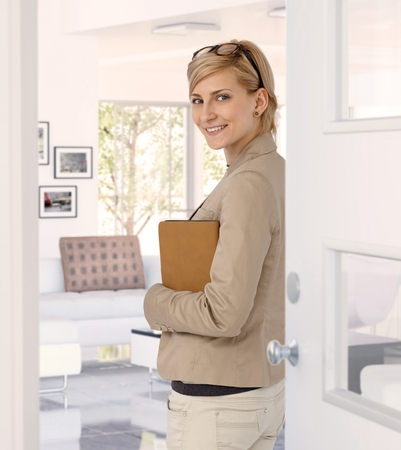 Happy casual caucasian blonde businesswoman standing at home doorway, wearing glasses, folder in hand. Smiling, standing, looking at back camera. photo