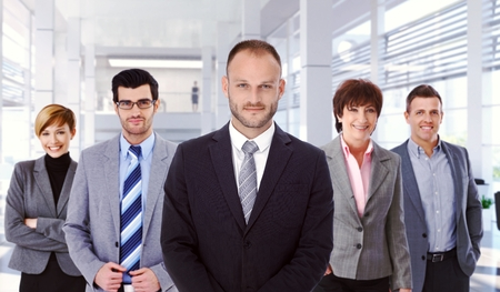 indoor photo: Group portrait of successful, determined business team at office with boss in front. Smiling, standing, looking at camera, wearing suit.