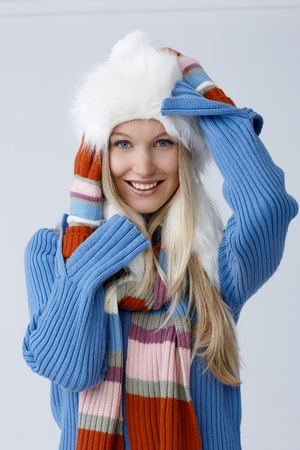 Happy blonde woman in fur hat smiling, looking at camera. photo