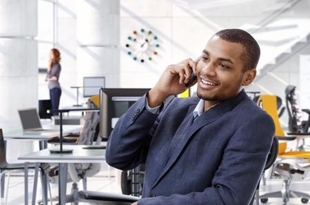 hombre sentado: Feliz, sonriente, exitoso asesor afro-americana de negocios hablando por teléfono móvil mientras estaba sentado en la mesa de oficina, brillante, traje sin corbata. Foto de archivo