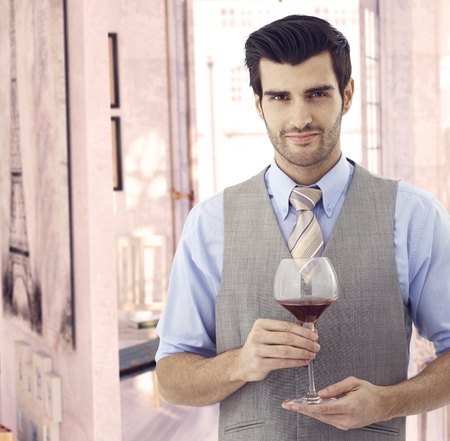 bristly: Handsome elegant young caucasian man with glass of wine at Paris retro home. Smiling standing, bristly, looking at camera. Suit and tie. Copyspace.