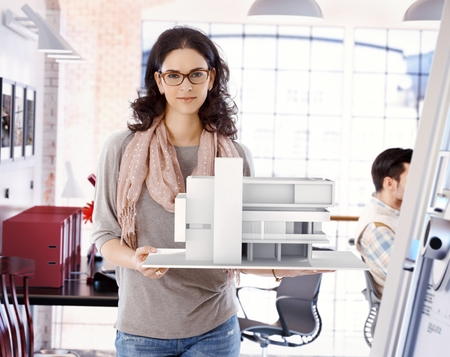 Casual caucasian attractive female architect with scale model of a building plan, standing, holding, wearing glasses, looking at camera, smiling at office.