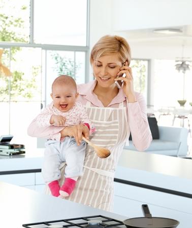 ama de casa: Feliz,, ama de casa caucásica en la cocina con el bebé en la mano, hablando por teléfono ocasional. De pie, ocupado, cocinar, con delantal, sosteniendo una cuchara de madera.