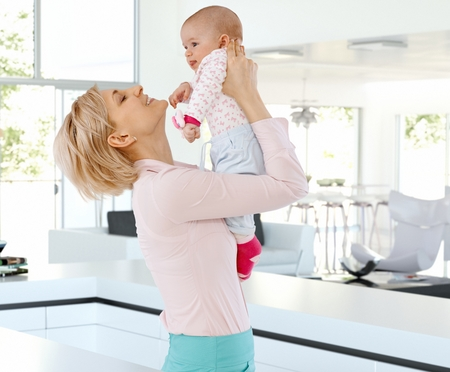 Happy casual blonde caucasian mother with cute baby at bright home indoors. Holding, raising, joy, family, smiling, standing. photo