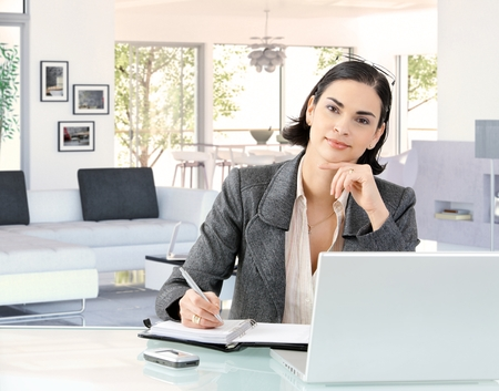 personal computer: Portrait of elegant smart caucasian businesswoman at home desk, wearing suit, sitting in front of laptop computer, personal business organizer and pen in hand. Hand under chin, looking at camera, smiling. Stock Photo
