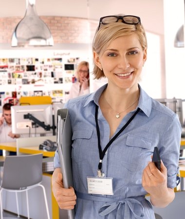 name tag: Happy caucasian casual blonde assistant worker at business office, standing, holding a folder, wearing glasses and a name card, tag, Smiling, looking at camera.