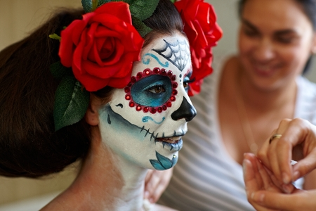 make up artist: Makeup artists in work making a Halloween makeup - mexican Santa Muerte mask.