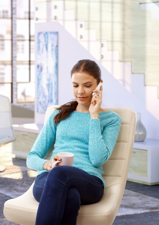 designer chair: Young casual caucasian brunette girl sitting at designer home in beige leather chair, mug in hand, using mobile phone. Small smile, calling, indoors,