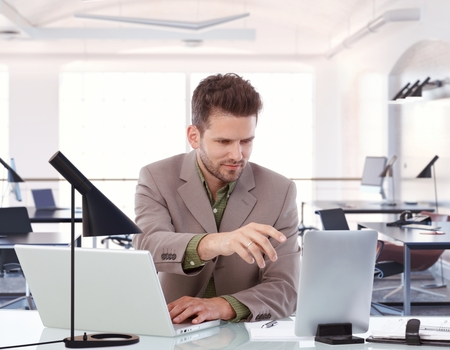 bristly: Young, bristly caucasian businessman working at business office desk on tablet and laptop. Sitting, looking at screen, reaching out, touchscreen, suit, typing.